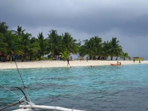 Photo prise d'une bateau d'une plage de sable blanc avec des palmiers aux philippines