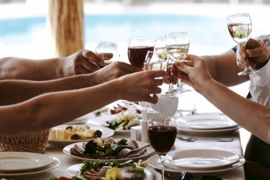 Table de restaurant avec des mains qui trinque avec des verres remplis.