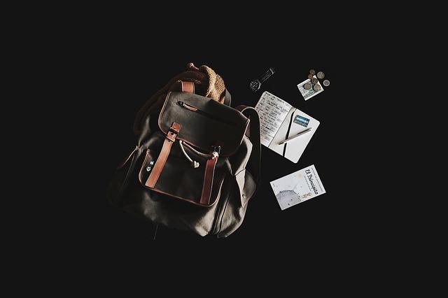 Photo sur fond noir avec un sac a dos en cuir et tissus avec des affaires tels que de la monnaie, un carnet une montre.