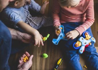 Deux enfants et un homme démontant un jeux de construction