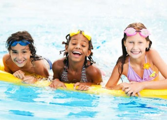 Trois enfants souriants sur une grande bouée jaune.