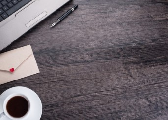 Bureau de couleur sombre en bois avec un ordianteur portable en haut à gauche, un café un stylo et une enveloppe avec un cœur rouge.