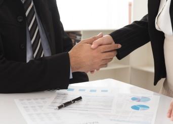 Deux mains professionnels qui se sert la main autour de plans.