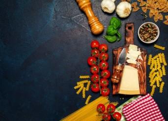 Table sombre, avec des aliments éparpillées tels que des pâtes, des tomates, des épices etc...