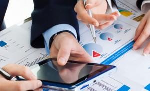 deux paires de mains autour de papiers, plans et tablettes