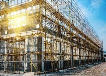 Murs en construction d'une grand bâtiment en longueur entouré d'échafaudage.