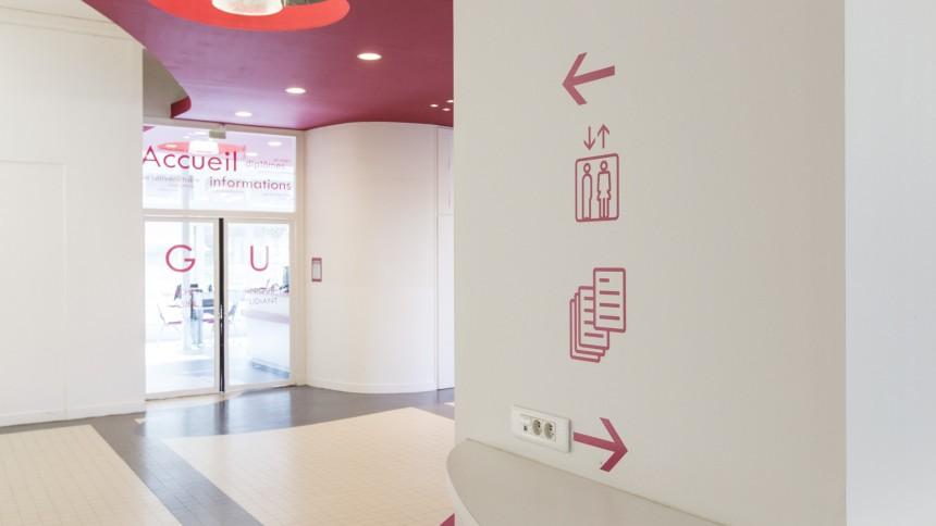 Grand hall aux murs blancs, ayant des indications de couleur rose rouge.