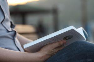 Un homme tient un livre ouvert à la moitié dans ses mains